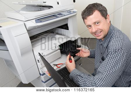 Man  Repairing A Printer At Business Place At Work