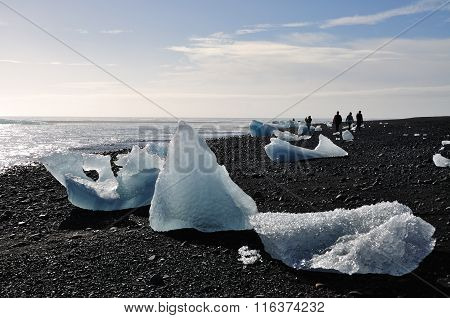 Jokulsarlon Beach With Icebergs And Silhouettes Of People