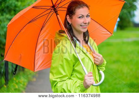 Beautiful Young Brunette Woman With An Orange Umbrella Closeup