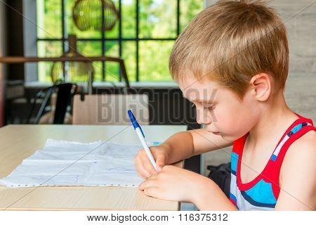 Portrait Of A Boy At The Table Drawing A Pictures