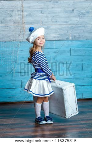 girl in vest holding a suitcase