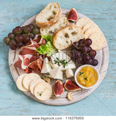 Ham, Cheese, Grapes, Figs, Nuts, Bread Ciabatta, Cracker, Jam On White Wooden Board  On Bright Woode