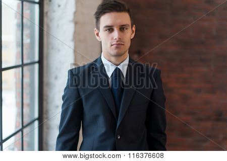 Portrait of a confident young businessman standing in office.