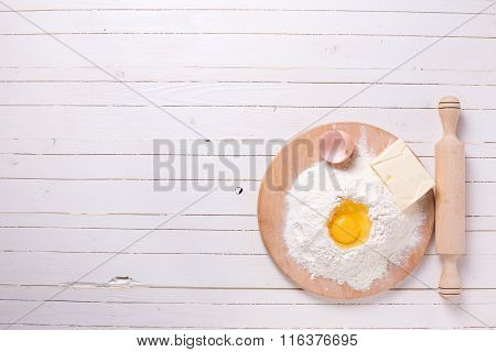 Ingredients for dough - flour on wooden board egg butter