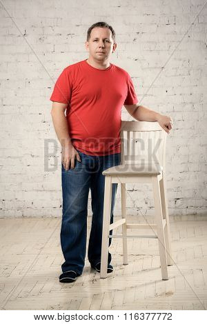 Man In A Red T-shirt Stands Near A Chair In Studio