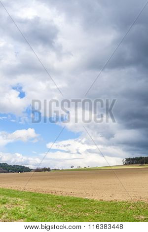 Dark Clouds And Blue Sky Over Field