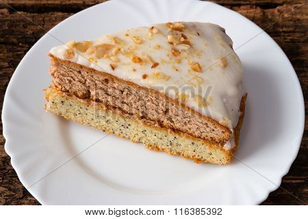 Cake On A White Plate On A Wooden Background