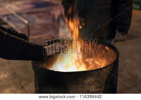 Homeless man warming his hands by a fire