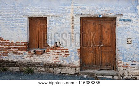 Exterior Of An Old Village House With Closed Vitnage Door And Window.
