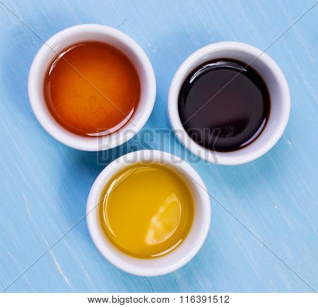 olive oil, soy sauce, sesame oil standing on a wooden table