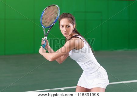 Portrait of a young woman playing tennis on court.