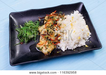 Rice, fried vegetables and fish. The finished dish on a wooden table