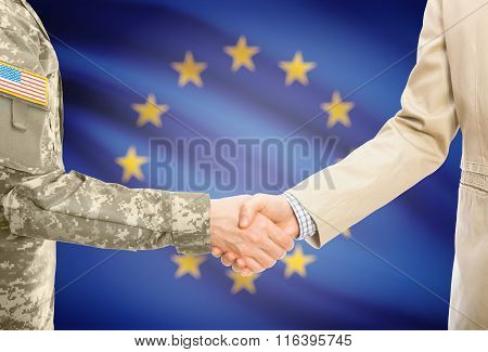 Usa Military Man In Uniform And Civil Man In Suit Shaking Hands With National Flag On Background - E