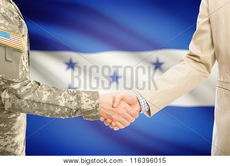 Usa Military Man In Uniform And Civil Man In Suit Shaking Hands With National Flag On Background - H