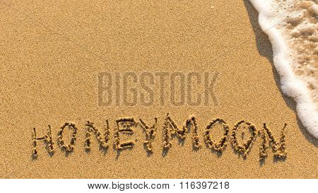 Honeymoon - word drawn on the sand beach with the soft wave.