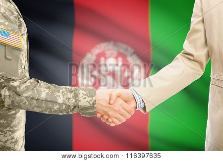 Usa Military Man In Uniform And Civil Man In Suit Shaking Hands With National Flag On Background - A