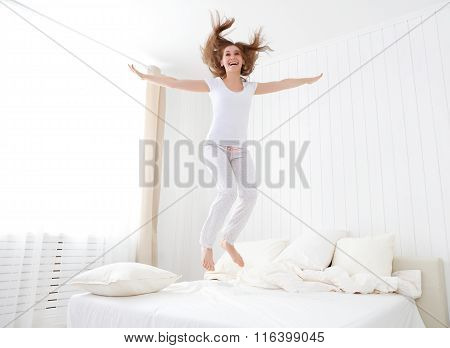 Happy Girl Jumping And Having Fun In Bed