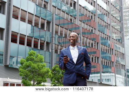 Businessman Walking With  Cell Phone In The City