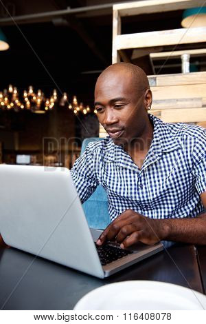 Black Guy Working On Laptop At A Cafe