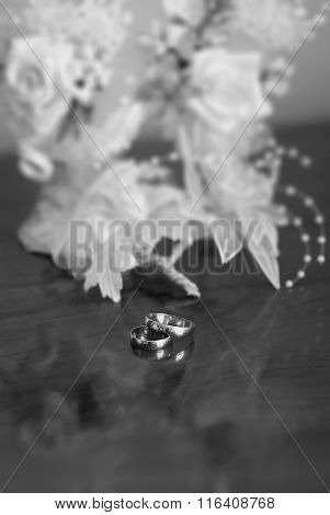 Wedding Rings With White Flowers On A Wooden Background