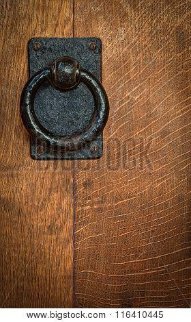 Old Black Metal Circular Knocker On Oak Door