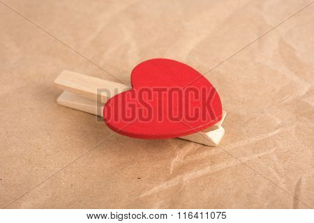 Heart-shaped clothes peg on craft paper