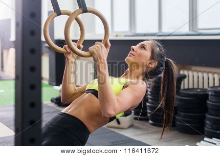 Fit woman going pull-ups with gymnastic rings in gym