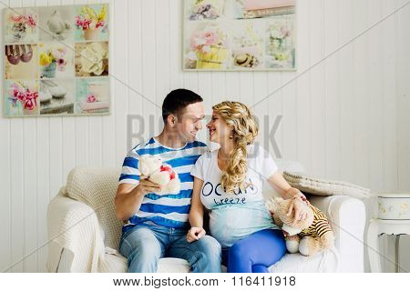Couple With Pregnant Woman Relaxing On Sofa Together.