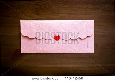 Valentine's Day message sealed in an envelope. Pink color envelope sealed with heart shaped sticker. Valentines day concept.