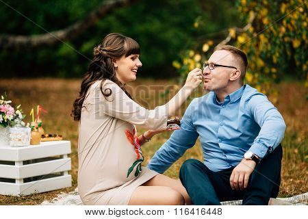 Young Beautiful Pregnant Woman Lovely Feeds Her Handsome Husband With Cake On Picnic.
