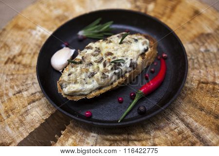 Home baked hot sandwich with mushrooms, cheese, onion on a cast-iron pan on a wooden background