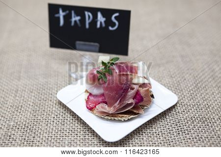 Fresh delicious Spanish tapas with hamon with fresh herbs and strawberries with poster TAPAS on the  wooden background . Great background for restaurant, cafe.