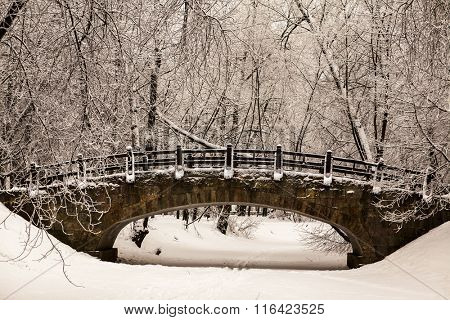Beautiful old stone bridge of  winter forest in the snow at sunset frosty days. Trees covered in frost and snow
