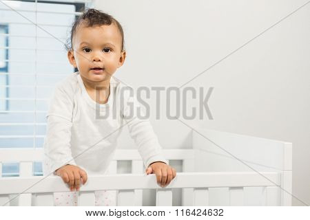 Cute baby standing in the crib in bedroom