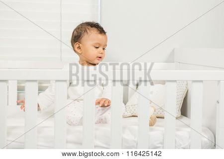 Cute baby sitting on the crib