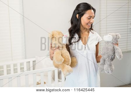 Smiling brunette holding plushs in bedroom