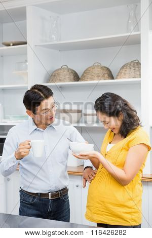 Happy expectant couple in the kitchen having breakfast