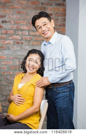 Portrait of happy expectant couple at home