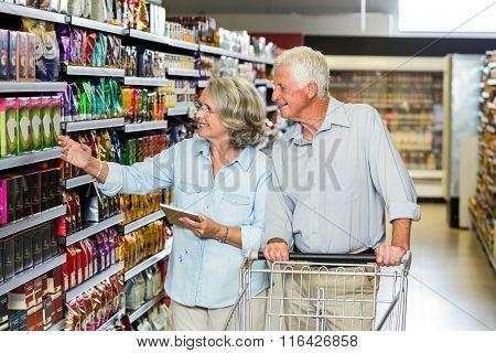 Smiling senior couple buying food at the supermarket