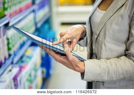 Woman using tablet pc in aisle in supermarket