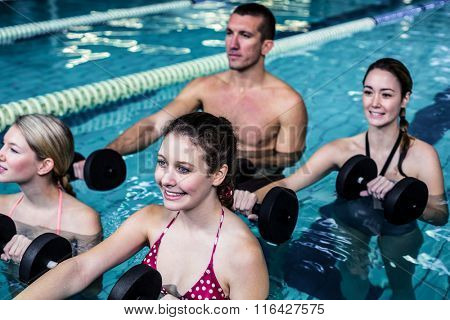 Fit people doing an aqua aerobics class in swimming pool