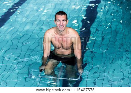 Fit smiling man cycling alone in the pool