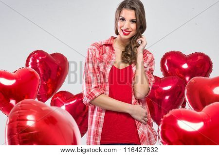 Adorable young woman surrounded by red Valentine's balloons