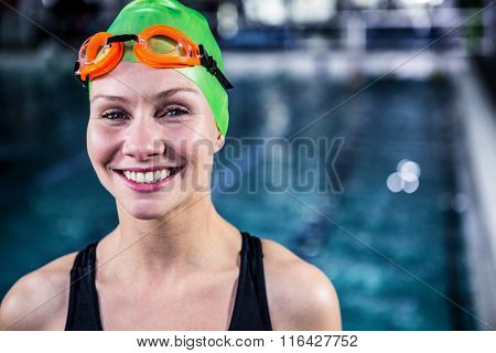 Portrait of a woman swimmer looking the camera in swimming pool