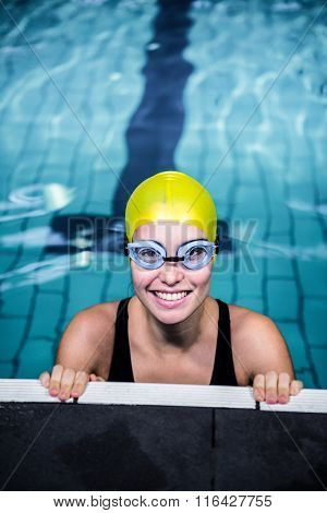 Smiling swimmer woman lean on the edge of the swimming pool