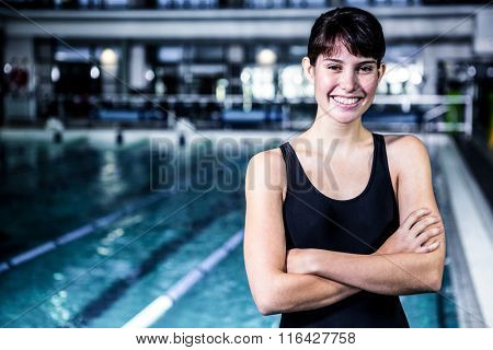 Smiling swimmer woman with arms crossed in swimming pool