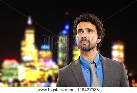 Businessman with city at nighttime on the background