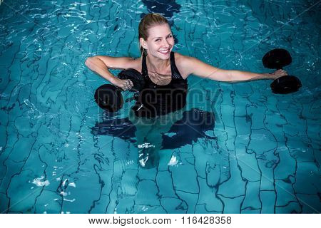 Fit smiling woman holding weights in the swimming pool