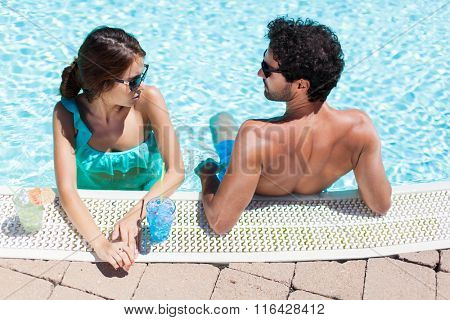 Couple drinking a cocktail on the poolside