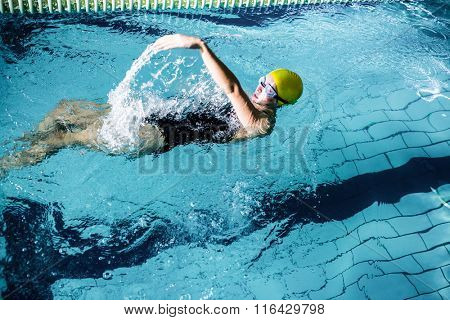 Fit female swimmer doing the back stroke in swimming pool